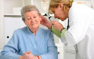 врач осматривает грибок в ухе пациента